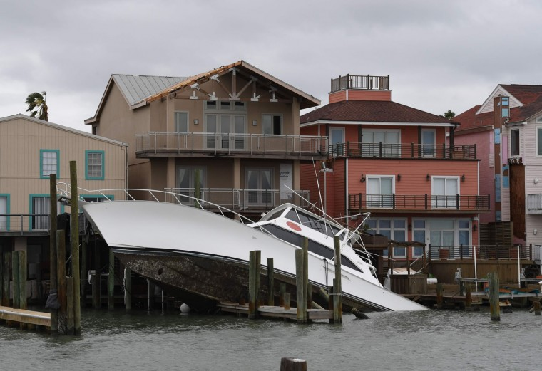 A sunken boat lies submerged in front houses after Hurricane Harvey hit Port Aransas, Texas on August 27, 2017. Hurricane Harvey hit the Texas coast with forecasters saying its possible for up to three feet of rain and 125 mpg wind. (Mark Ralston/AFP/Getty Images)