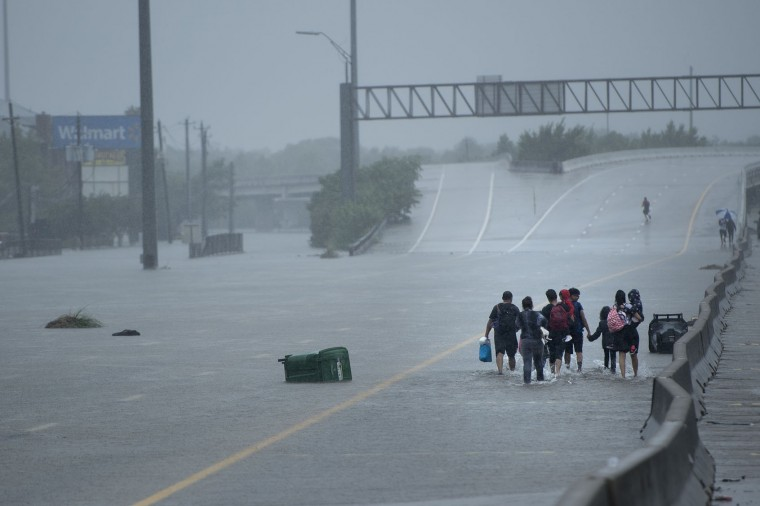 Evacuation residents from the Meyerland area walk onto an I-610 overpass for further help during the aftermath of Hurricane Harvey August 27, 2017 in Houston, Texas. Hurricane Harvey left a trail of devastation Saturday after the most powerful storm to hit the US mainland in over a decade slammed into Texas, destroying homes, severing power supplies and forcing tens of thousands of residents to flee. (Brendan Smialowski/AFP/Getty Images)