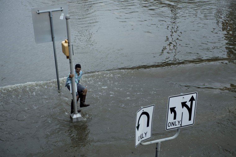 A man dodges a wake in flood waters during the aftermath of Hurricane Harvey August 27, 2017 in Houston, Texas. Hurricane Harvey left a trail of devastation after the most powerful storm to hit the US mainland in over a decade slammed into Texas, destroying homes, severing power supplies and forcing tens of thousands of residents to flee. (Brendan Smialowski/AFP/Getty Images)