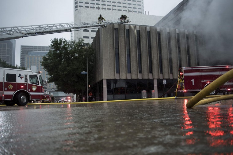 Firefighters put out a fire during the aftermath of Hurricane Harvey on August 28, 2017 in Houston, Texas. (Brendan Smialowski/AFP/Getty Images)