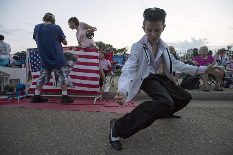 Nathan Pittorf shows off his best Elvis Presley impersonation during a candlelight vigil for Presley at Graceland, his Memphis home, on Tuesday, Aug. 15, 2017, in Memphis, Tenn. Fans from around the world are at Graceland for the 40th anniversary of the rock n' roll icon's death. Presley died Aug. 16, 1977. (AP Photo/Brandon Dill)