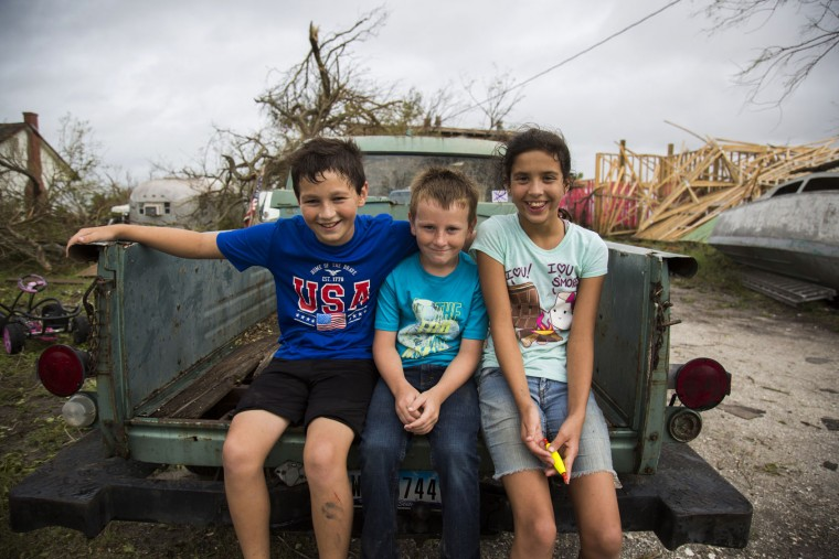 Kyler Carpenter, from left, Cory Carpenter and Laela Carpenter sit in the back of a truck in front of Laela's home in Bayside, Texas, on Sunday, Aug. 27, 2017, near damage from Hurricane Harvey. (Olivia Vanni/The Victoria Advocate via AP)