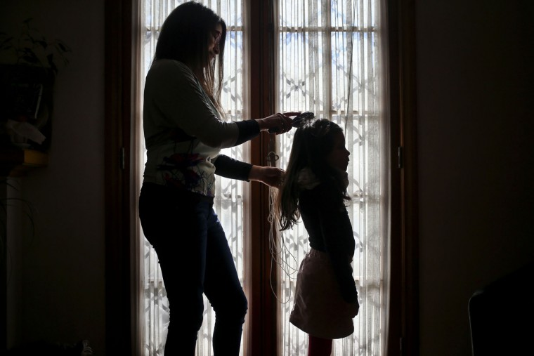 In this July 18, 2017 photo, Monica Flores combs her daughter's hair at their home in Santiago, Chile. Flores was questioned by Chilean police at the airport because the records didn't match: she had left on holidays abroad with a son and returned to the country with a daughter who went by the name Luna. In front of airport authorities, she had to explain that her 6-year-old registered as a boy identified as a girl. (AP Photo/Esteban Felix)