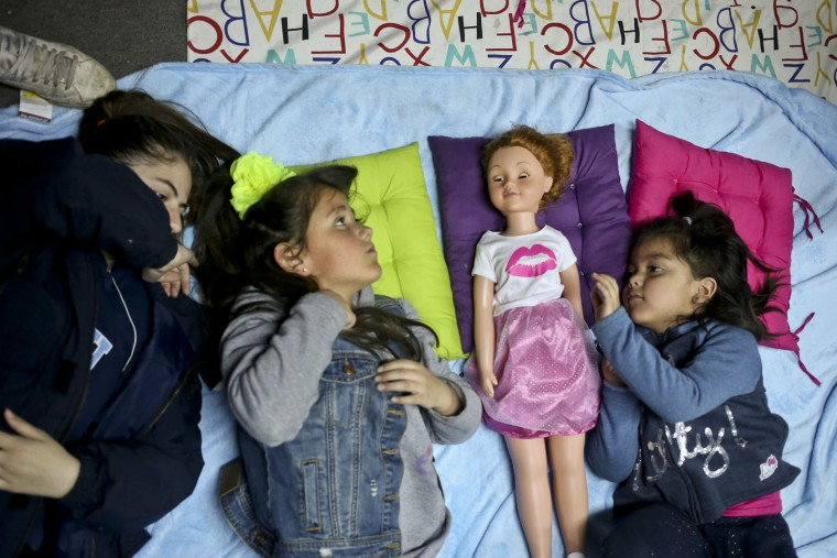 "In this July 8, 2017 photo, transgender girls Selenna, second from left, and Mathilda, right, play with a doll as their mothers attend a meeting on gender identity at a bookshop in Santiago, Chile. Selenna said she never liked celebrating her birthday because she would always get toy cars. ""Maybe they didn't notice it,"" said Selenna. ""But I was always (a girl)."" (AP Photo/Esteban Felix)"