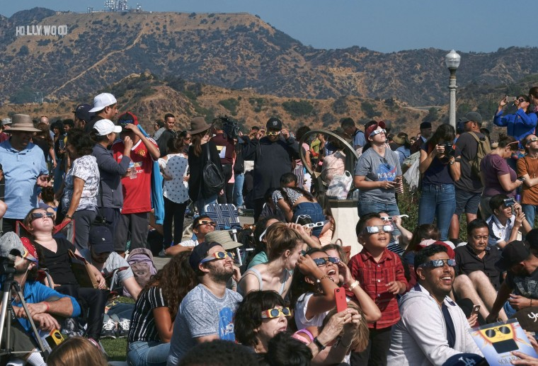 A large crowd gathers in front of the Hollywood sign at the Griffith Observatory to watch the solar eclipse in Los Angeles Monday, Aug. 21, 2017. (AP Photo/Richard Vogel)