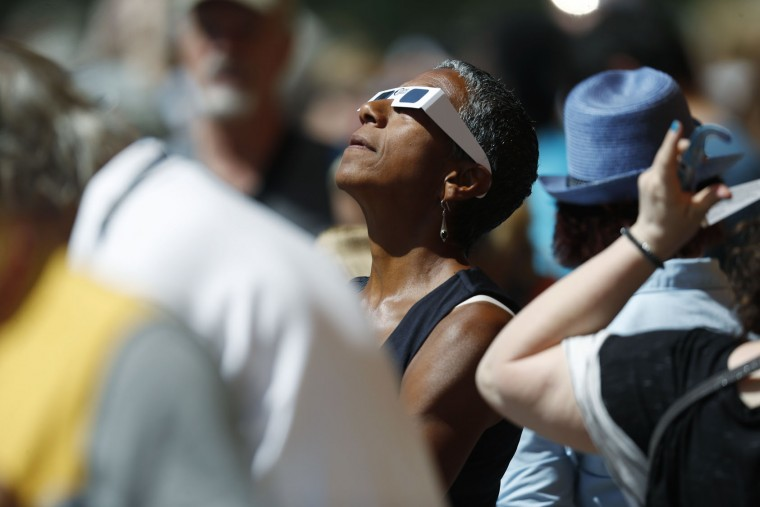 Happy Haynes of Denver uses glasses as she joins others residents as they gather at the Denver Museum of Nature and Science to observe the partial solar eclipse as it passes over City Park in east Denver on Monday, Aug. 21, 2017. While only a partial eclipse in Denver--92 percent--other parts of the intermountain West experienced a total eclipse. The last time a total eclipse crossed the entire continental United States was June 8, 1918. (AP Photo/David Zalubowski)