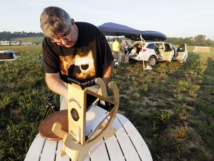Mark Renz, of Rochester, N.Y., sets up his Sunspotter, a device for viewing the solar eclipse, at his campsite Monday, Aug. 21, 2017, on the Orchard Dale historical farm near Hopkinsville, Ky. The location, which is in the path of totality, is also at the point of greatest intensity. (AP Photo/Mark Humphrey)