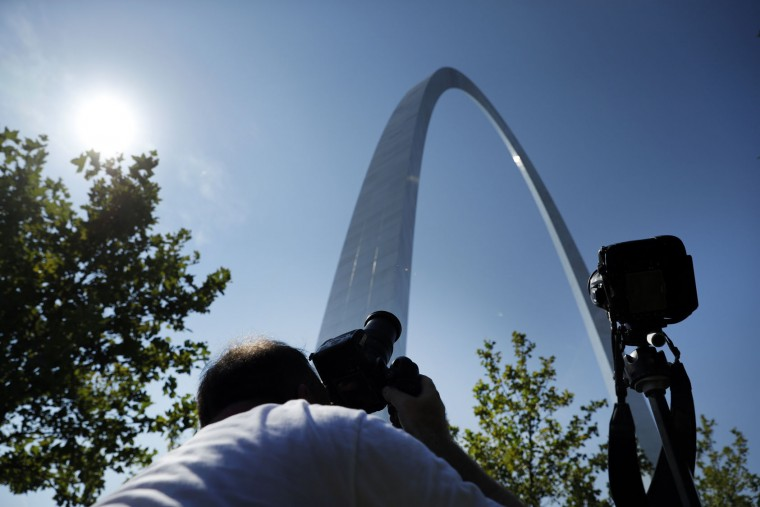 Jason Arbaugh, of Austin, lines up his shot for the solar eclipse at the Gateway Arch on Monday, Aug. 21, 2017, in St. Louis. The Gateway Arch sits a few miles outside of the path of totality. (AP Photo/Jeff Roberson)