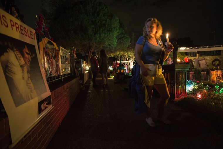 A woman participates in a candlelight vigil for Elvis Presley at Graceland, Presley's Memphis home, on Tuesday, Aug. 15, 2017, in Memphis, Tenn. Fans from around the world are at Graceland for the 40th anniversary of his death. Presley died Aug. 16, 1977. (AP Photo/Brandon Dill)