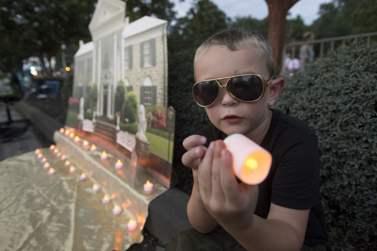 Mason Zwosta, from Independence, Ky., holds an electric candle during a candlelight vigil for Elvis Presley at Graceland, Presley's Memphis home, on Tuesday, Aug. 15, 2017, in Memphis, Tenn. Fans from around the world are at Graceland for the 40th anniversary of the rock n' roll icon's death. Presley died Aug. 16, 1977. (AP Photo/Brandon Dill)