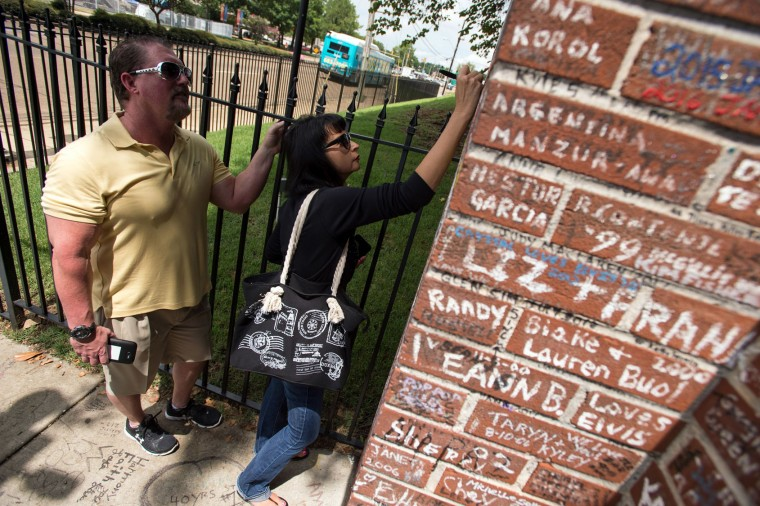 Jeff Moore, left, and Rebecca Moore sign their names on the wall outside Graceland, Elvis Presley's Memphis home, on Tuesday, Aug. 15, 2017, in Memphis, Tenn. Fans from around the world are at Graceland for the 40th anniversary of his death. Presley died Aug. 16, 1977. (AP Photo/Brandon Dill)