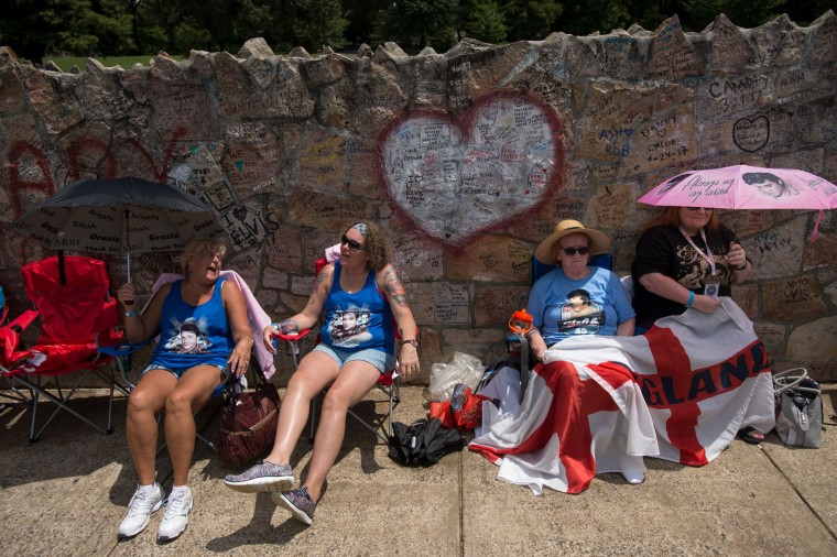Elvis fans, from left, Debby Twigg, Dustie Lundy, Ann Lawlor, and Lynn Lawlor wait in line outside Graceland, Elvis Presley's Memphis home, on Tuesday, Aug. 15, 2017, in Memphis, Tenn. Fans from around the world are at Graceland for the 40th anniversary of his death. Presley died Aug. 16, 1977. (AP Photo/Brandon Dill)