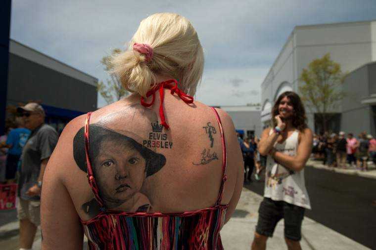 Sonya Man, left, sports a tattoo of a young Elvis Presley outside while talking with her son Bobbi Man, right, at Elvis Presley's Memphis near Graceland, Elvis Presley's Memphis home, on Tuesday, Aug. 15, 2017, in Memphis, Tenn. Sonya traveled from her home in London, England to be married at Graceland on Aug. 14. Fans from around the world are at Graceland for the 40th anniversary of his death. Presley died Aug. 16, 1977. (AP Photo/Brandon Dill)
