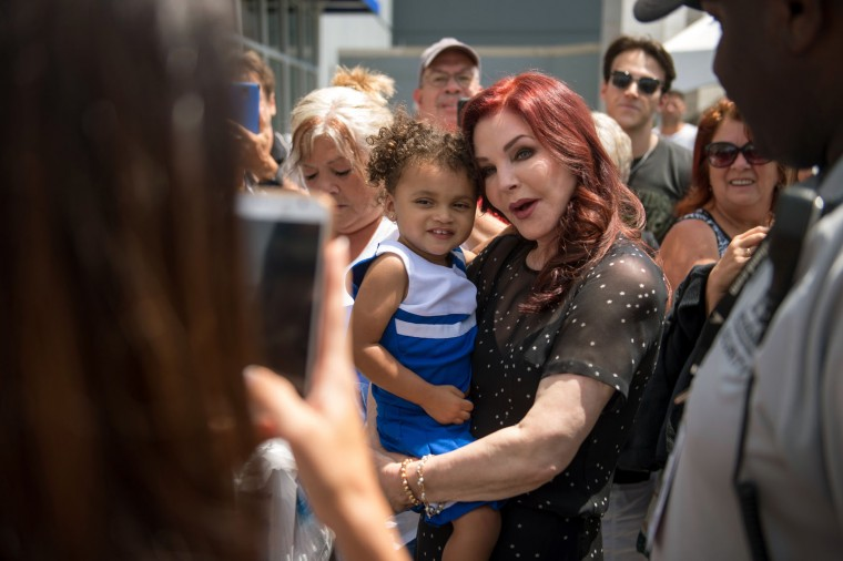 Priscilla Presley, center right, former wife of Elvis Presley, holds a child while greeting fans at Elvis Presley's Memphis near Graceland, Elvis Presley's Memphis home, on Tuesday, Aug. 15, 2017, in Memphis, Tenn. Fans from around the world are at Graceland for the 40th anniversary of his death. Presley died Aug. 16, 1977. (AP Photo/Brandon Dill)