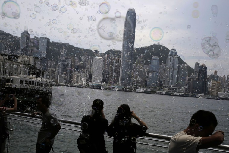 "People take photographs of bubbles during an art display titled ""Bubble Up"" created by Japanese artist Shinji Ohmaki in Hong Kong, Wednesday, Aug. 2, 2017. (AP Photo/Kin Cheung)"