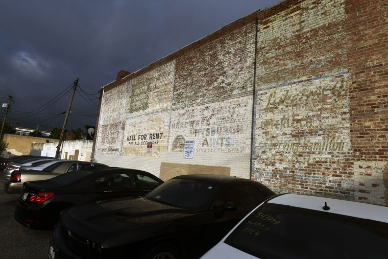 Several fading painted ads are grouped together on a wall on Hamilton Avenue. (Kim Hairston/Baltimore Sun)