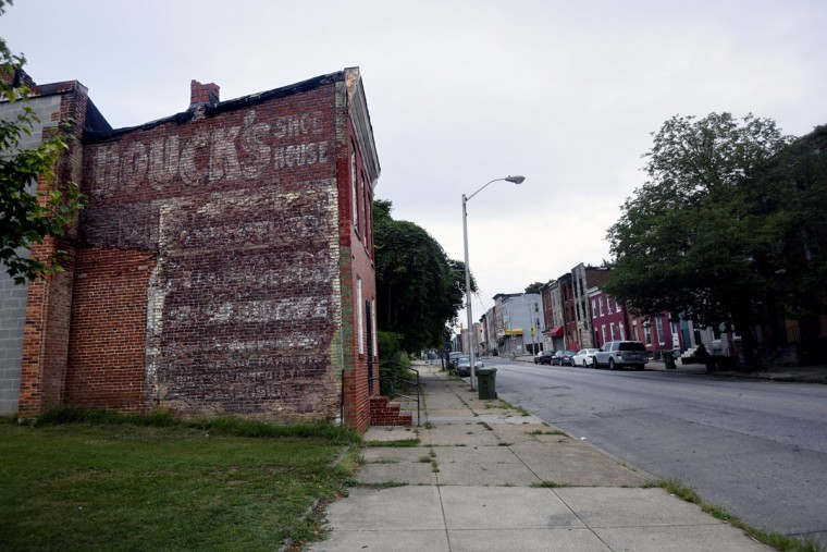 A ghost sign on the side of a rowhouse on Greenmount Avenue advertises Houck's Shoe House. (Kim Hairston/Baltimore Sun)