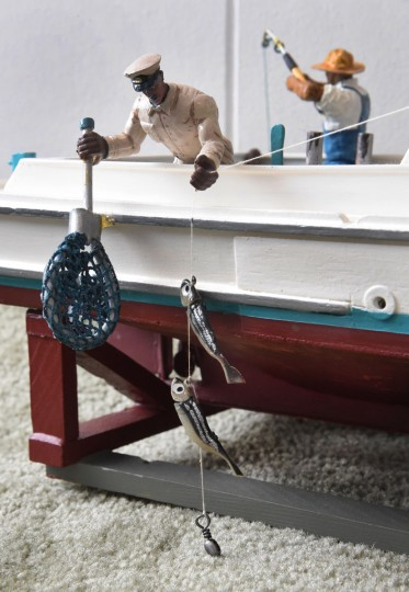 "Capt. Frank Gross, one of the first African-American captains on the Chesapeake, is shown leaning over the side of his Bay-built, the ""Miss Myrtle,"" to net a fish. Norman Gross, his son, honors his father and the other African-American watermen he knew by recreating, in miniature, their workboats and lives on the Chesapeake. (Amy Davis / The Baltimore)"