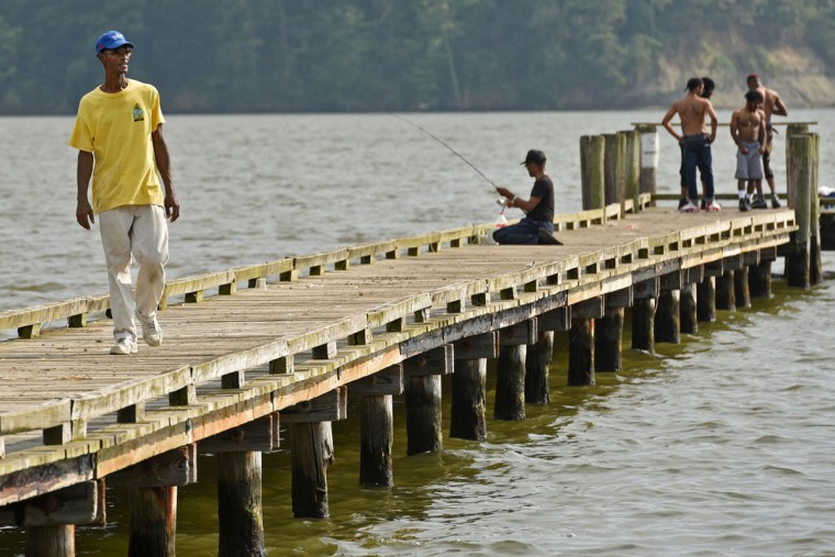 Norman Gross, 58, walks on the pier at County Wharf, as others fish in the Rhode River. Gross has been visiting this spot since he was a child, when he used to catch perch, croaker, snapper blues, and trout here. (Amy Davis / The Baltimore Sun)