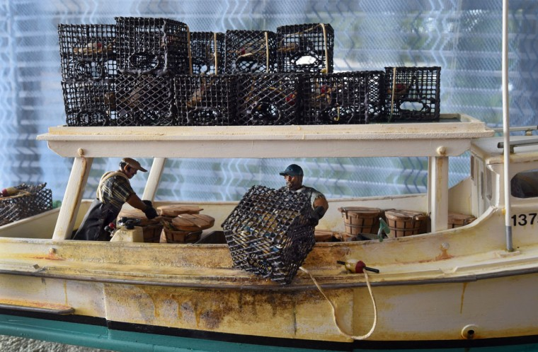 "Buck Gross, Norman Gross' brother, is depicted on his crab boat, the ""Little Rascal,"" hoisting a crab pot as he works with a friend, Pee Wee Matthews. Norman Gross made each crab pot out of small mesh wire, and carved each bushel basket from wood. Gross, 58, builds model boats that pay homage to an earlier generation of African-American watermen on the Chesapeake. (Amy Davis / The Baltimore Sun)"