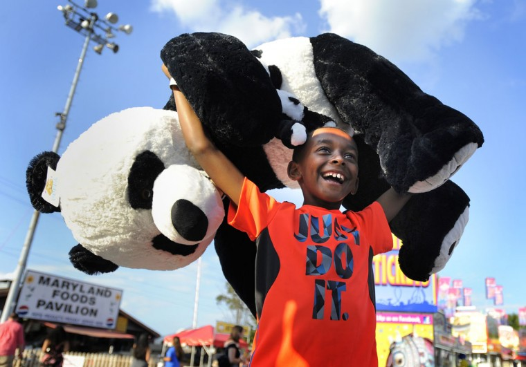 Nile Ross, 8, of Baltimore, sinks his final basketball shot to win this giant panda at the fair. (Lloyd Fox/Baltimore Sun)
