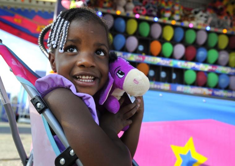 Laylah Price, 3, of Edgewood, hugs the prize she won in the bean bag game. (Lloyd Fox/Baltimore Sun)