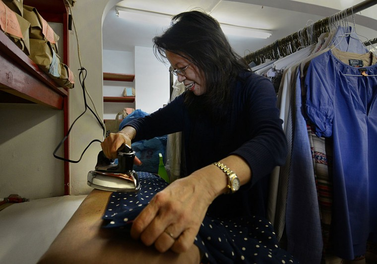 Shirley Tsao, whose family owns TC Wing Laundry in Roland Park, irons a blouse.