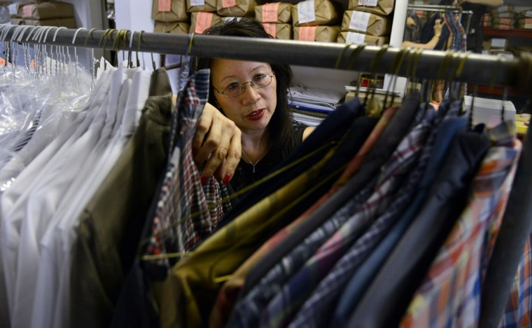 Shirley Tsao looks through a rack of cleaned shirts in her family's business, the T.C. Wing Chinese Hand Laundry in Roland Park.