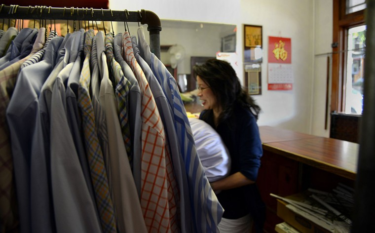 Shirley Tsao, whose family owns TC Wing Laundry in Roland Park, rushes by a rack of clean shirts.