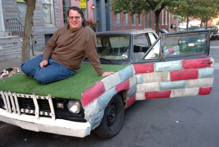 The Formstone Car, a 1969 Plymouth Valiant, was created by Phil Minion, who is laying on its astroturf hood. He lives in southwest Baltimore, in Sowebo. (Barbara Haddock Taylor/Baltimore Sun archive)