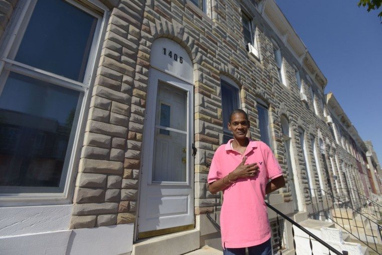 """Donna Johnson stands on the front step of her mother's house on E. Lanvale Street. """"This block's been like this as long as I can remember,"""" she said. (Christina Tkacik/Baltimore Sun)"""