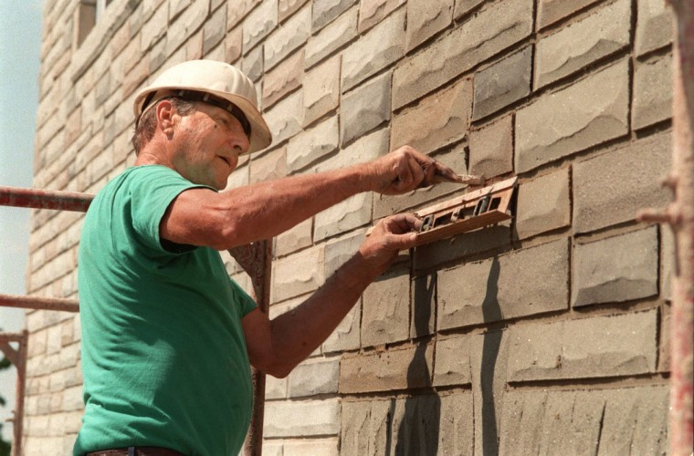 """Aado Vaigro, an Estonian-born craftsman who puts formstone on houses for his company, Modern Stone, working on a corner attached home in North Point Village. He has been doing formstone since 1950, but in recent years the trend has been more toward removing the fake stone covering. Vaigro uses level as straight edge to carve lines imitating mortar between """"stone"""" blocks. (Amy Davis/Baltimore Sun archives)"""