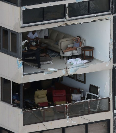 SAN JUAN, PUERTO RICO - SEPTEMBER 25: People sit in their apartment with the window blown out by the winds of Hurricane Maria as it passed through the area last week on September 25, 2017 in San Juan Puerto Rico. Maria left widespread damage across Puerto Rico, with virtually the whole island without power or cell service. (Photo by Joe Raedle/Getty Images)