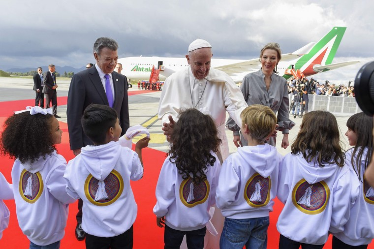 This handout picture released by the Colombian Presidency shows Pope Francis next to President Juan Manuel Santos and his wife First Lady Maria Clemencia Rodriguez, greeting children upon the pontiff's arrival to Bogota. CESAR CARRION/AFP/Getty Images