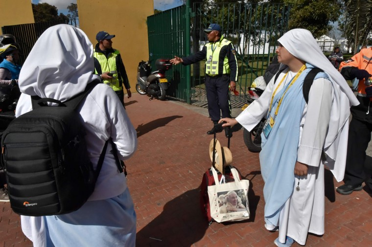 A nun stands with her luggage, which includes a bag with a picture of Pope Francis, as she waits for the arrival of the pontiff in Bogota. AFP PHOTO / Rodrigo BUENDIA