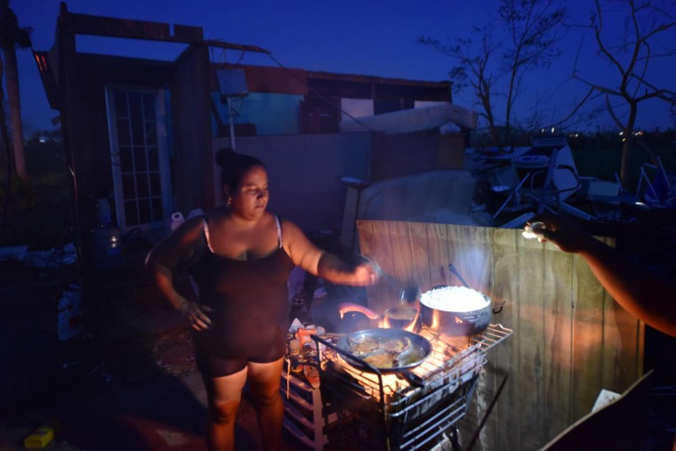 Maria prepares food during nightfall next to her home, destroyed by Hurricane Maria, in Toa Alta, Puerto Rico, on September 25, 2017. The US island territory, working without electricity, is struggling to dig out and clean up from its disastrous brush with the hurricane, blamed for at least 33 deaths across the Caribbean. (AFP PHOTO / HECTOR RETAMAL)