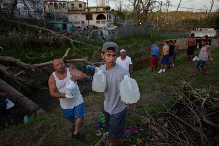 People carry water in bottles retrieved from a canal due to lack of water following passage of Hurricane Maria, in Toa Alta, Puerto Rico, on September 25, 2017. The US island territory, working without electricity, is struggling to dig out and clean up from its disastrous brush with the hurricane, blamed for at least 33 deaths across the Caribbean. (AFP PHOTO / HECTOR RETAMAL)