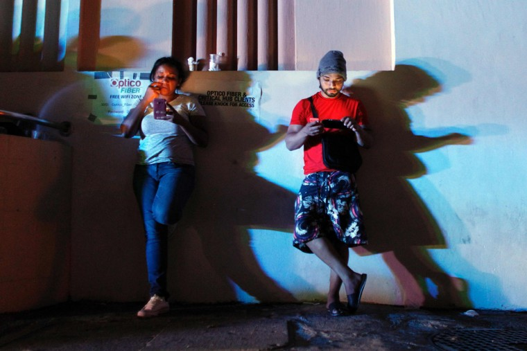 People use their cell phones at night in one of the few places with cell signal access in San Juan, Puerto Rico, on September 25, 2017, where a 7pm-6am curfew has been imposed following impact of Hurricane Maria on the island. (AFP PHOTO / Ricardo ARDUENGO)