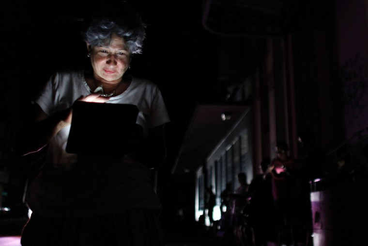 A woman uses her tablet at night in one of the few places with signal access in San Juan, Puerto Rico, on September 25, 2017, where a 7pm-6am curfew has been imposed following impact of Hurricane Maria on the island. (AFP PHOTO / Ricardo ARDUENGO)