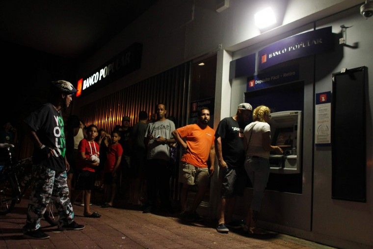 People make line at night at an ATM to withdraw money in San Juan, Puerto Rico, on September 25, 2017, where a 7pm-6am curfew has been imposed following impact of Hurricane Maria on the island. (AFP PHOTO / Ricardo ARDUENGO)