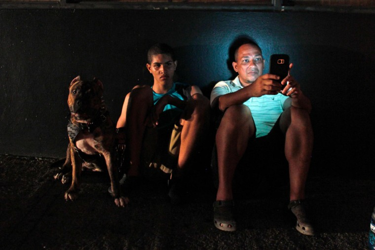 A man checks his cell phone next to a road at night in one of a few places with cell signal in San Juan, Puerto Rico, on September 25, 2017, where a 7pm-6am curfew has been imposed following impact of Hurricane Maria on the island. (AFP PHOTO / Ricardo ARDUENGO)
