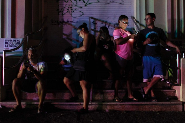People use their cell phones at night in one of the few places with cell signal in San Juan, Puerto Rico, on September 25, 2017, where a 7pm-6am curfew has been imposed following impact of Hurricane Maria on the island. (AFP PHOTO / Ricardo ARDUENGO)