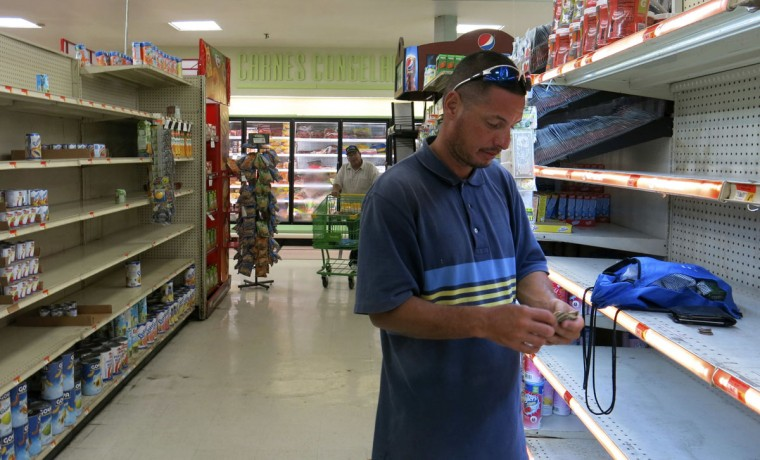 Christian Mendoza counts money in the aisle of a supermarket where he had hoped to buy water but only found cans of juice in San Juan, Puerto Rico, Monday Sept. 25, 2007. Bottled water was gone from stores throughout Puerto Rico in the few stores open five days after the earthquake. (AP Photo/Ben Fox)