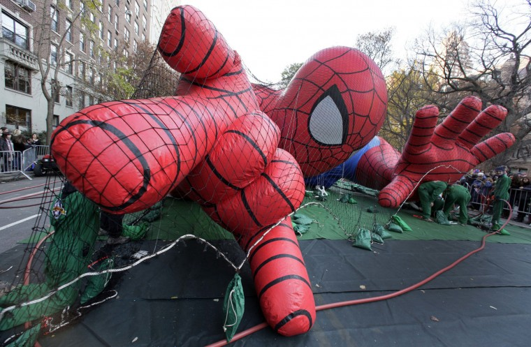 FILE - In this Nov. 21, 2012 file photo, workers inflate the Spider-Man balloon for the annual Macy's Thanksgiving Day Parade in New York. New York police say the Macy's Thanksgiving Day Parade balloon inflation viewing will end two hours early this year and anyone attending must be screened. Tens of thousands of people are expected to head to Central Park on Wednesday to watch the giant balloons take shape. (AP Photo/Richard Drew, File)