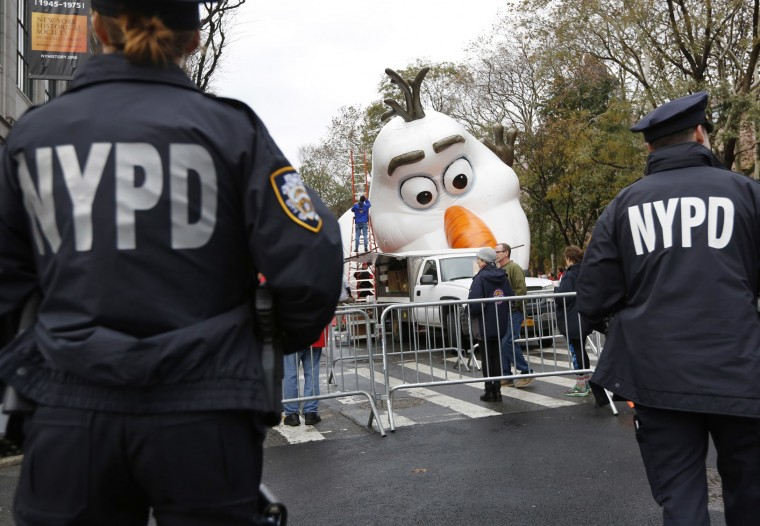 "Police officers stand near the site where a large balloon of Olaf, from the animated film, ""Frozen"", is being inflated for the Thanksgiving Day parade in New York, Wednesday, Nov. 22, 2017. Sand-filled sanitation trucks and police sharpshooters will mix with glittering floats and giant balloons at a Macy's Thanksgiving Day Parade that comes in a year of terrible mass shootings and a deadly truck attack in lower Manhattan. (AP Photo/Seth Wenig)"