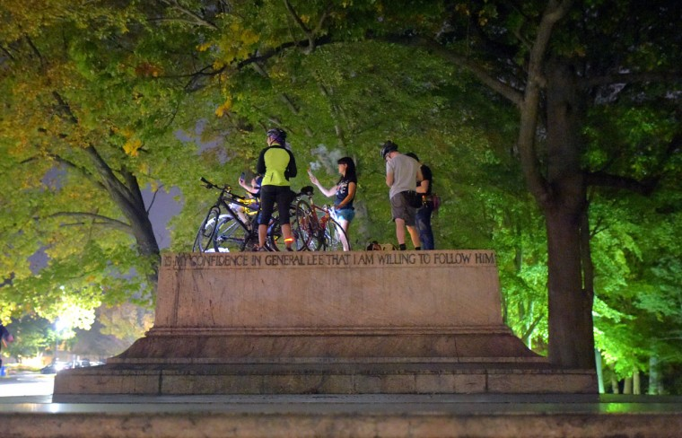 Bicyclists smudge on the base of one of Baltimore's removed confederate monuments at Wyman Park, on a bike run recognizing the second Baltimore Cease Fire weekend. (Karl Merton Ferron / Baltimore Sun Staff)
