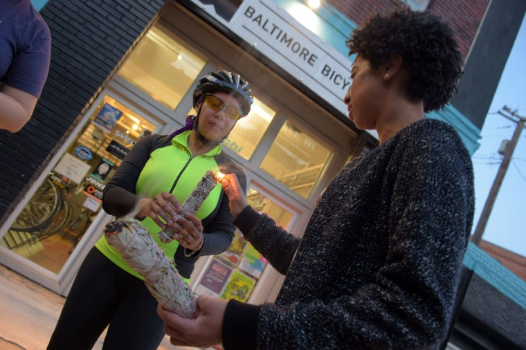 "Shelley Purnell of Walbrook gets her sage stick lit, by Stacie Henderson of Mt. Vernon at Baltimore Bicycle Works before riding to City Hall and Wyman Park to participate in ""smudging,"" on a bike run recognizing the second Baltimore Cease Fire weekend. (Karl Merton Ferron / Baltimore Sun Staff)"