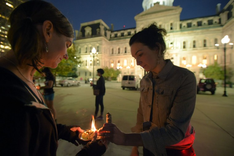 Jules O'Quinn of Remington (left) and Karen Mattes of Remington commence smudging during a stop at Baltimore's City Hall, on a bike run recognizing the second Baltimore Cease Fire weekend. (Karl Merton Ferron / Baltimore Sun Staff)