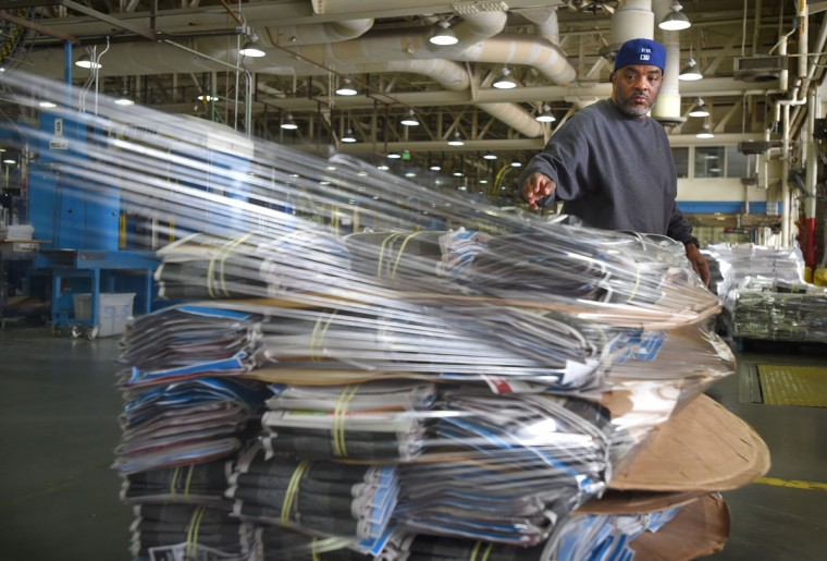 Edward Bowles uses a shrink wrap machine to wrap the newspapers before they are loaded onto trucks for delivery. (Lloyd Fox/Baltimore Sun)