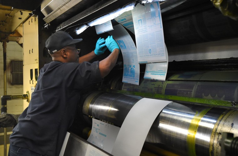 Mike Ball, a pressman, attaches the press plates before the paper is printed. The facility uses 26,000 gallons of black ink per year to print the paper. Enough to fill one Olympic-size swimming pool. (Lloyd Fox/Baltimore Sun)